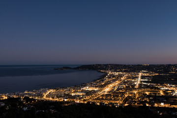 Seaside town just after sunset, city lights lit up