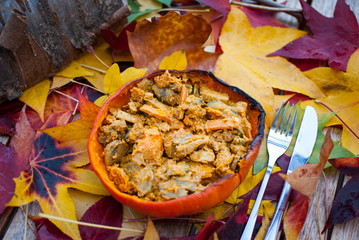 A bowl of vegan food in a pumpkin on a bed of colorful leafs