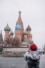 Unfocused girl taking picture of saint Basil's Cathedral in Moscow