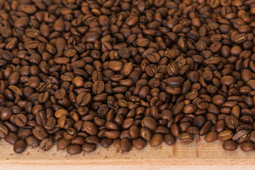 Closeup of fragrant roasted coffee beans on a wooden board. Selective focus. place for text.