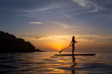 Woman paddle boarding on Pacific Ocean at sunset, La Jolla, San Diego, California, USA
