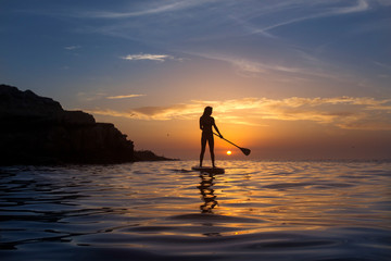 Woman paddle boarding on Pacific Ocean at sunset, San Diego, California, USA