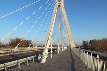 Rzeszow, Poland - 9 9 2018: Suspended road bridge across the Wislok River. Metal construction technological structure. Modern architecture. A white cross on a blue background is a symbol of the city.