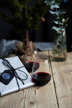 Two glasses of red wine sitting on a table next to some Christmas gifts.