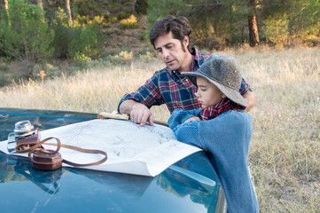 A father and his son leaning on a car watching a map in the forest