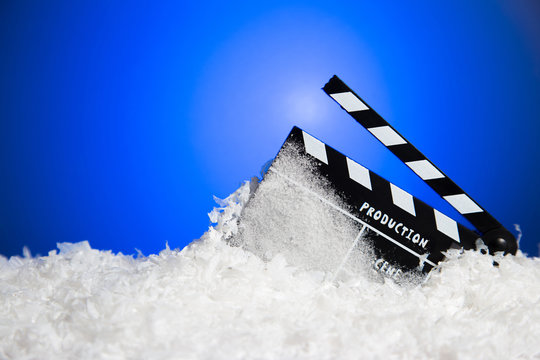 Frozen film clapper / clapperboard with copy space on blue background.
