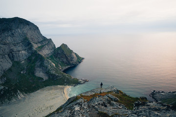 Tiny hiker overlooking beach on mountain in Norway