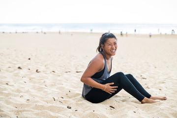 Happy female athlete sits on sandy beach, Oahu, Hawaii, USA