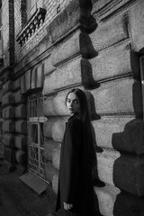 beautiful girl in black about the walls of the building