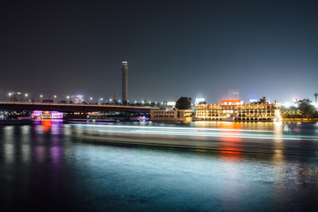 Cairo city center at night, long exposure with light trails of moving boats on the Nile river.