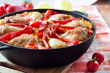 Chicken thighs and legs baked over a bed of rice and red bell pepper