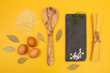 Cooking ingredients on bright yellow background