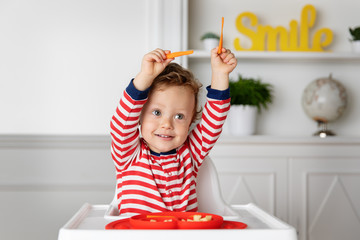 Funny toddler in high chair playing with carrot sticks