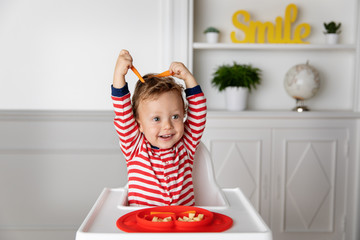 Funny baby in high chair playing with carrot sticks