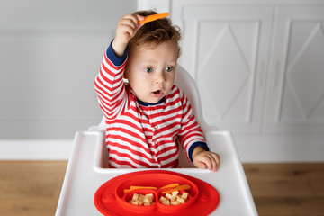 Toddler in high chair playing with finger food