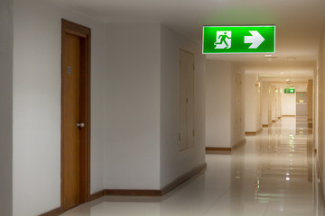 green emergency exit sign in hotel showing the way to escape Wall mural