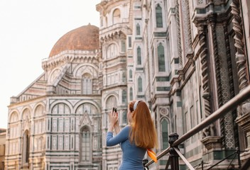 Back view portrait of redhead girl taking picture of Duomo in Florence