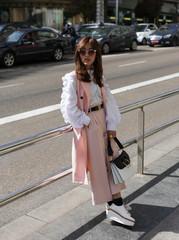 Trendy model in pink posing on street