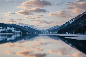 Evening dusk over the Lake Weissensee. Lake Weissensee with picturesque reflection in winter, Carinthia, Austria