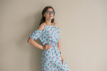young pretty sympathetic sexy girl in eyeglasses with loose hair in a blue dress with red flowers with a cut on her leg and stockings on a coffee background