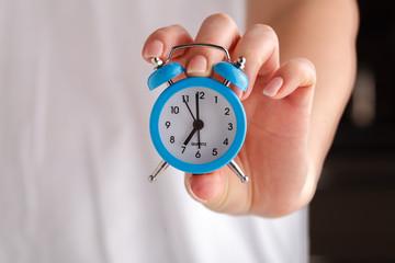 female hands holding alarm clock