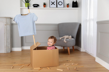 Toddler sitting in a cardboard box pretending it's a boat