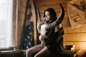 Portrait of yang dark style woman sits on wooden table in a cozy house with wooden walls, holds in hands, embraces a buffalo skull, light from a window and a warm lamp, is dressed in black and a hat, halloween costume, usa american flag on the background