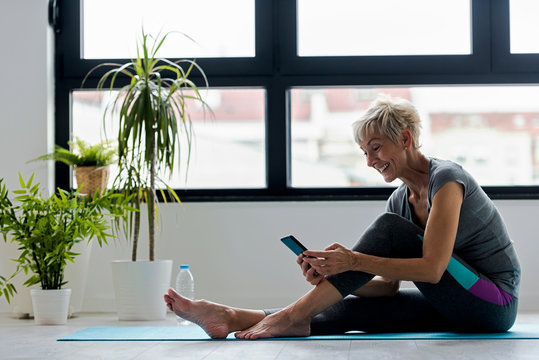 Senior active woman using smart phone at home after practicing yoga. The use of technology by the elderly.