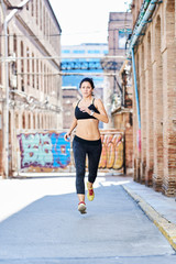Motivated sportswoman running in side street of urban city.