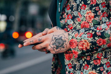 Tattooed handsome man with colourful flower jacket around the city.