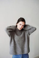 Young woman wearing oversize sweater against grey background
