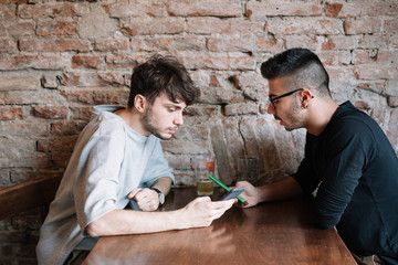 Men browsing smartphone in bar