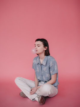 Woman making bubble from gum