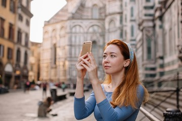Portrait of redhead girl taking picture with her phone in the street of Florence