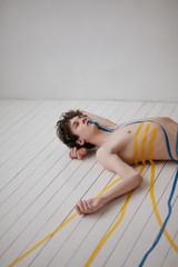 Shirtless man taped to floor