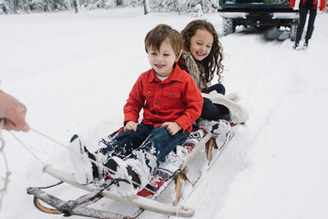 happy kids ride old wood sled in snow