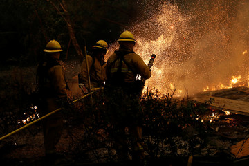 Firefighters battle to save homes after mandatory evacuations were ordered at the Camp Fire in Paradise