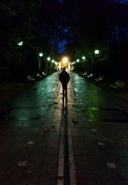 Man walking alone throug a dark street at night