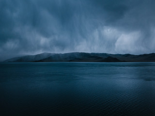 storm clouds above tolbo nuur lake with a mountain range in mongolia