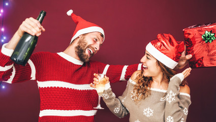 Happy couple drinking champagne at christmas time - Young people having fun celebrating xmas holidays - Love, relationship and youth lifestyle