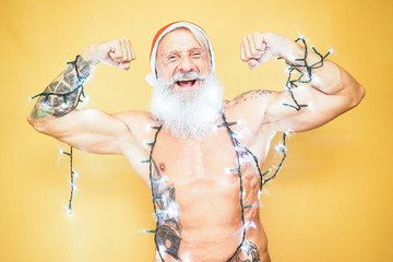 Happy fit santa claus equiped with white christmas lights - Trendy beard hipster senior wearing xmas equipment - Celebration and holidays concept