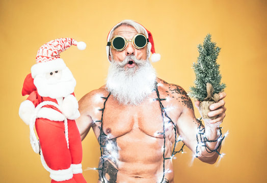 Happy fit santa claus equiped with white christmas lights - Trendy beard hipster senior holding a mini santa claus puppet and xmas tree - Celebration and holidays concept