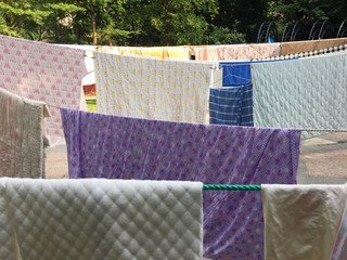 A variety of quilts, drying in public areas outdoor