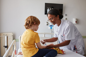Doctor female giving attention and care to child in a hospital room