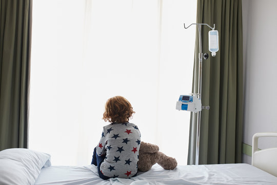 Silhouette of a patient child sitting on a hospital bed with his teddy bear