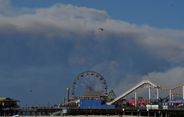 Clouds of smoke appear from the Woolsey Fire to the north in Malibu as a helicopter flies over the  Santa Monica Beach Pier in Santa Monica