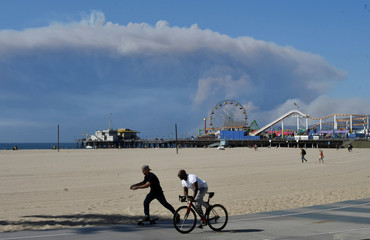 Clouds of smoke appear from the Woolsey Fire to the north in Malibu and over the Santa Monica Pier as people walk through Venice Beach