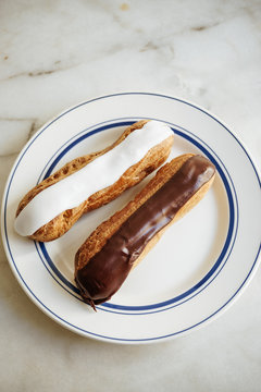 Two eclairs on a plate, ready to be eaten