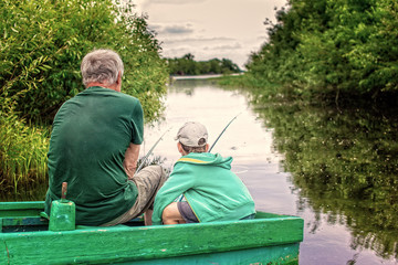 boy and an old man sitting in a boat with a fishing rod. grandfather and grandson fishing together. Back view. Copy space for your text