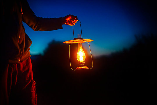 hand holds a large old lamp in the dark. man holding the vintage lamp with a candle outside. Copy space for your text